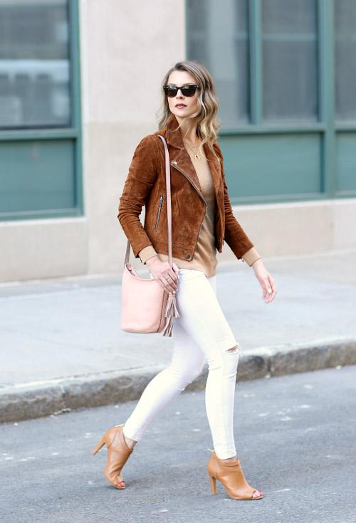 Девушка в белых джинсах и коричневой куртке.