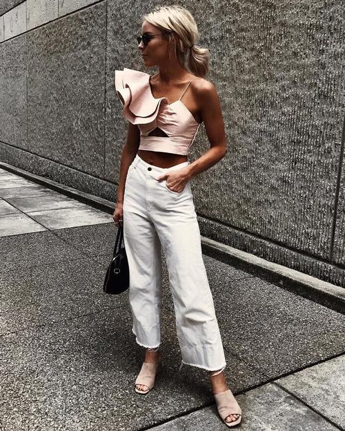 Девушка в белых укороченных джинсах и асимметричном топе.
