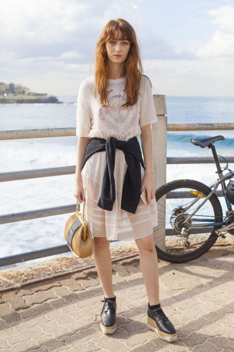 Девушка в бежевом платье и толстовке повязанной на талии