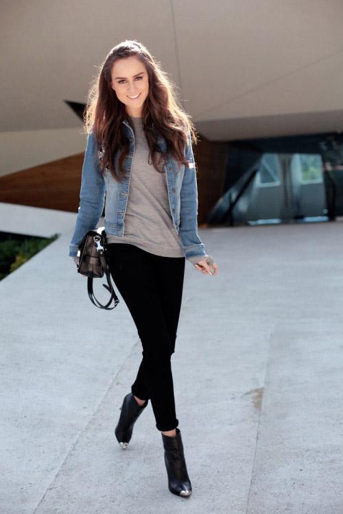 Девушка в черных джинсах, ботильонах, серой футболке и голубой джинсовке