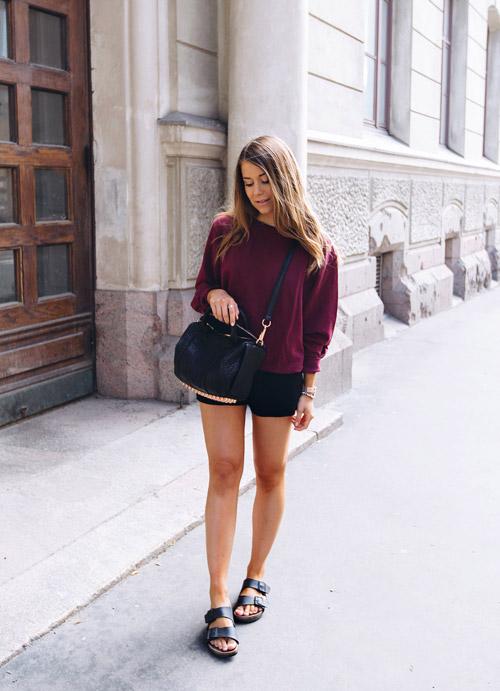 Девушка в черных шортах и фиолетовом джемпере.