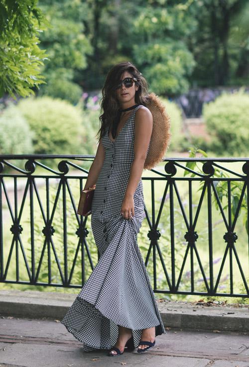 Девушка в длинном клетчатом платье, босоножках и с огромной шляпой за спиной.