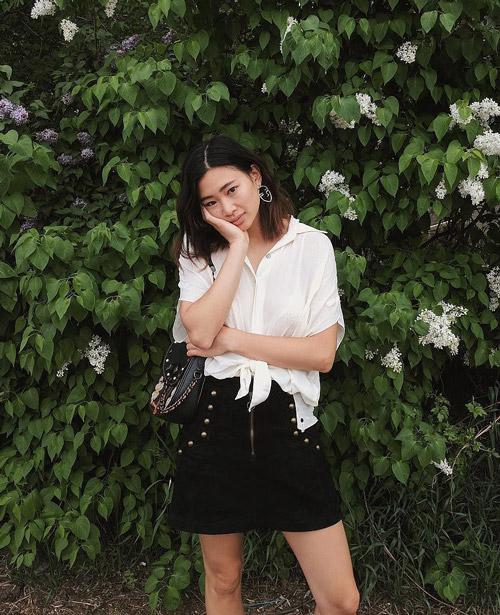 Девушка в джинсовой мини юбке и белой блузке.
