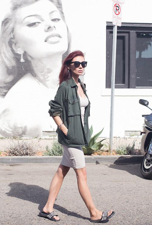 Девушка в обтягивающем платье, куртке милитари и шлепанцах.