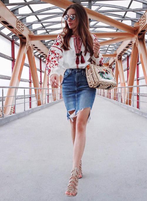 Девушка в рваной джинсовой юбке и блузе народного стиля.