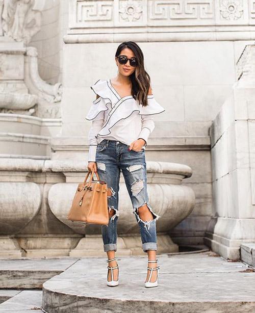 Девушка в рваных джинсах и блузе с воланами.