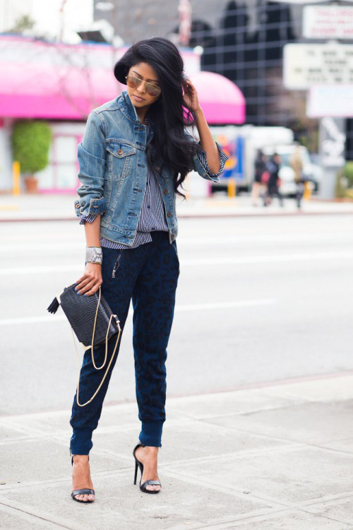 Девушка в спортивных штанах, полосатой рубашке, джинсовке и черных босоножках