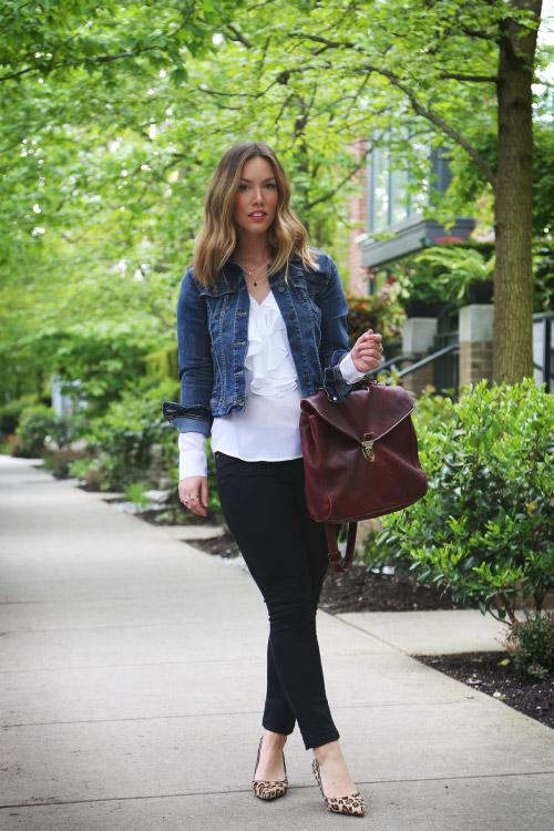 Девушка в темных джинсах, леопардовых лодочках, белом топе и джинсовке