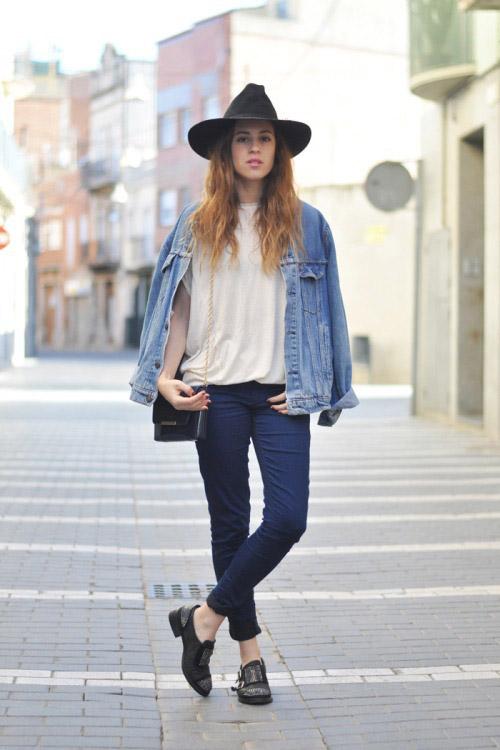 Девушка в темных джинсах, светлой джинсовке и черной шляпе