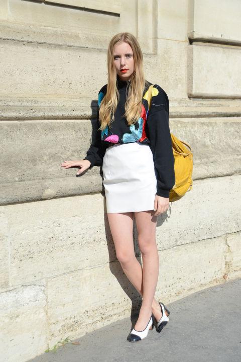 Девушка в толстовке с ярким принтом и белой юбке