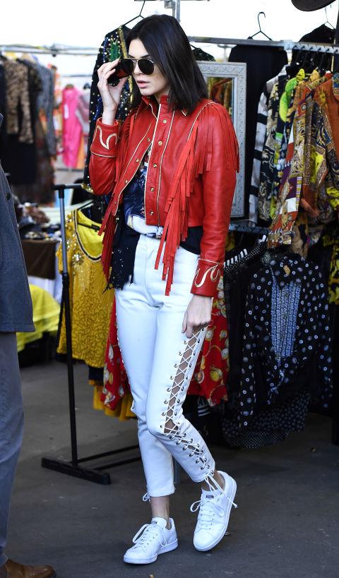 Кендалл Дженнер в капри со шнуровкой по бокам, красная косуха и кроссовки