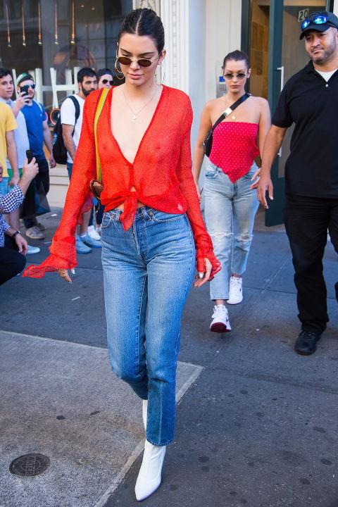 Кендалл Дженнер в красной блузке и джинсах