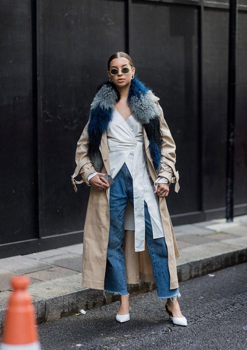 Девушка в белой блузке, синии джинсы и бежевый плащ с меховым воротником