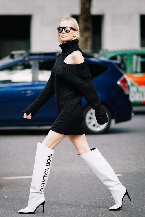 Девушка в черном мини платье с воротником и открытыми плечами, белые высокие сапоги на шпильке