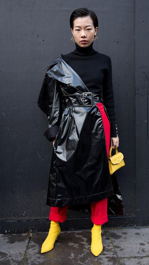 Девушка в черной водолазке, лакированный плащ и красные брюки