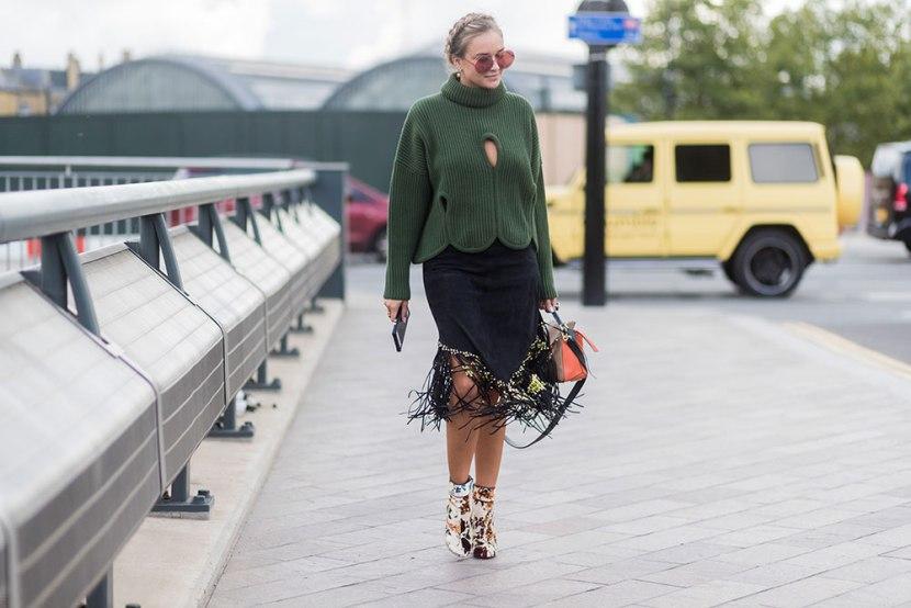 Девушка в черной юбке с бахромой и зеленый свитер с воротником, цветочные ботильоны