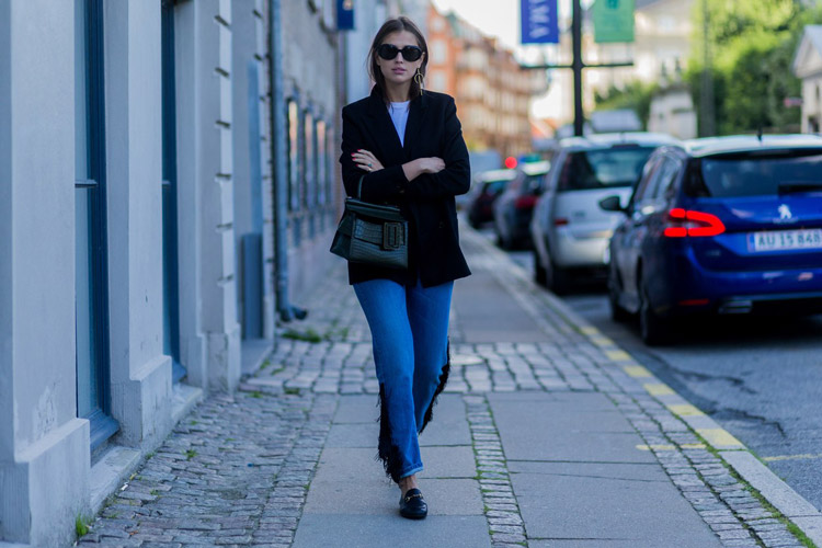 Девушка в джинсах с бахромой и темносинем пиджаке