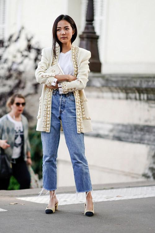 Девушка в джинсах с необработанными краями и светлом жакете