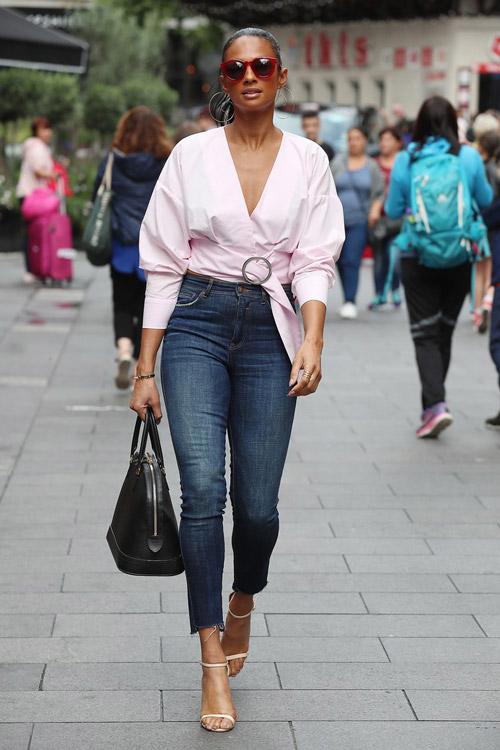 Девушка в джинсах скинни с завышенной талией и ассиметричном топе