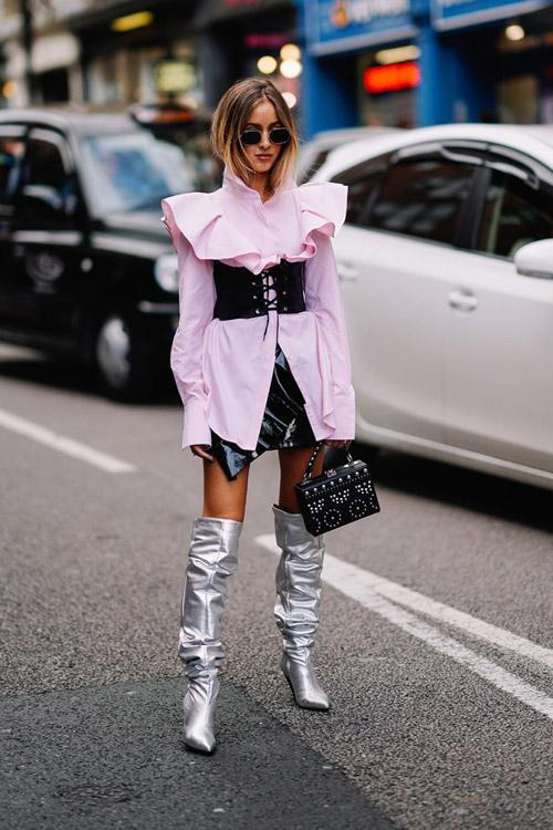 Девушка в кожаной мини юбке, розовая рудашка с корсетом и серебристые сапоги