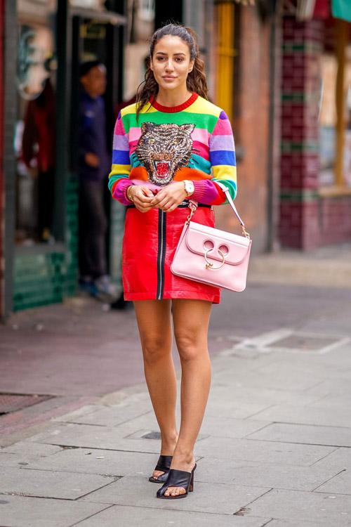 Девушка в красной кожаной юбке и ярком полосатом свитшоте
