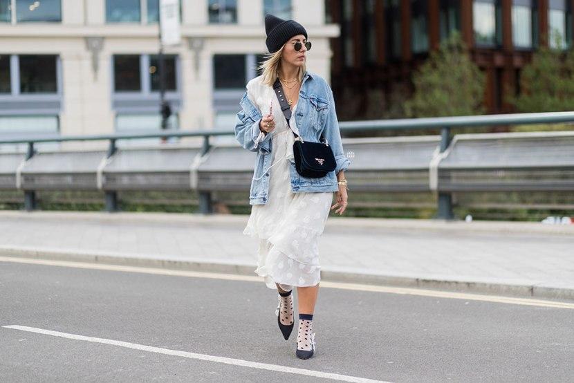 Девушка в легком платье ниже колен, джинсовая куртка и шапка