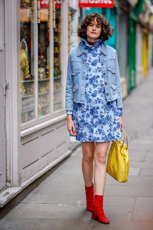 Девушка в мини платье с цветочным принтом, джинсовая куртка и красные ботильоны
