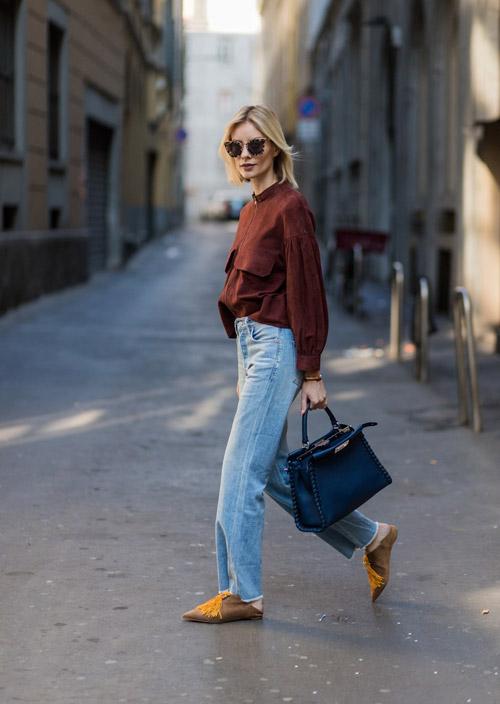 Девушка в прямых синих джинсах и остроносых тапочках