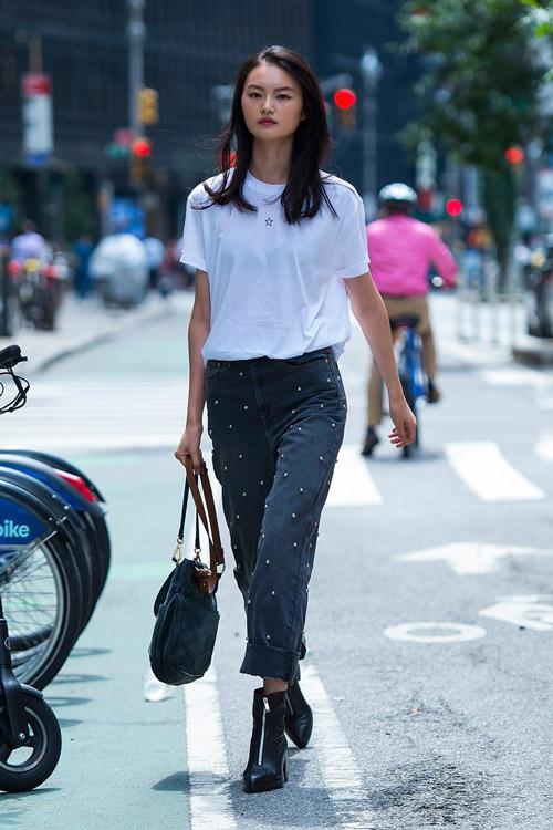Девушка в серых джинсах с жемчужинами, белой футболке и ботильонах