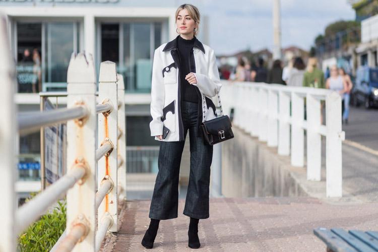 Девушка в серых широких джинсах, классических лодочках и светлом пальто