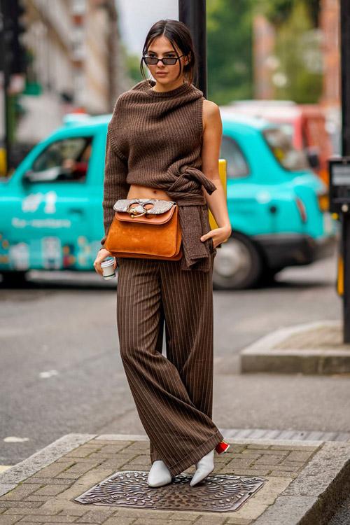 Девушка в широких коричневых брюках и свитере, белые ботильоны и рыжая сумка