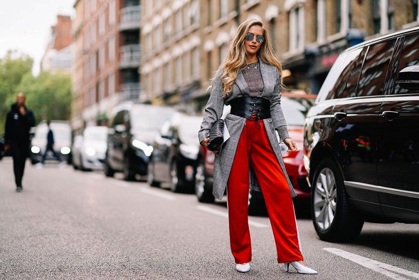 Девушка в широких красных штанах, серый кардиган с корсетом, белые туфли