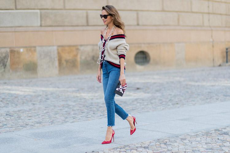 Девушка в синих джинсах, кардигане и красных лодочках