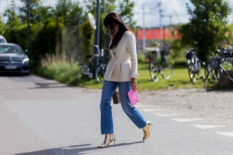 Девушка в синих джинсах, светлом жакете и золотистых ботильонах
