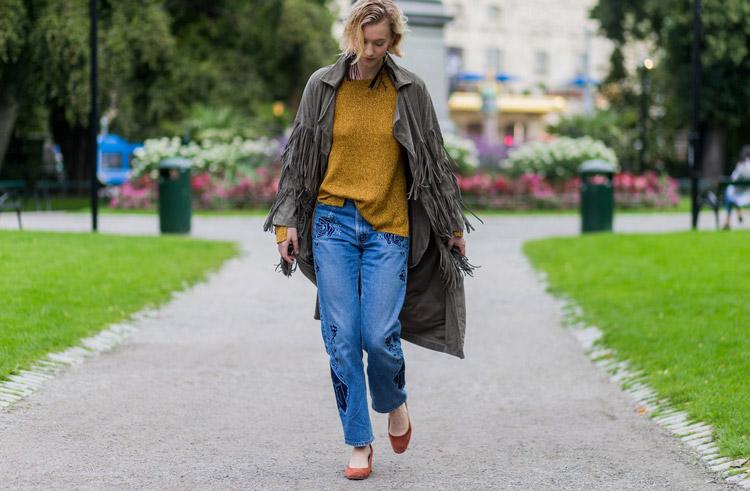 Девушка в синих джинсах, желтом свитшоте и плаще с бахромой