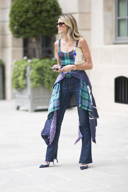Девушка в темных джинсах, клетчатом топе и лодочках