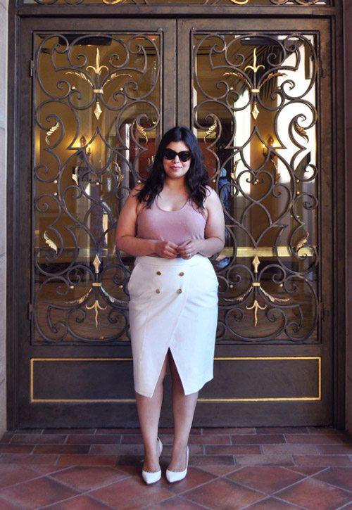 Полная девушка блогер в белой юбке с разрезом, грязно-розовом топе и лодочках