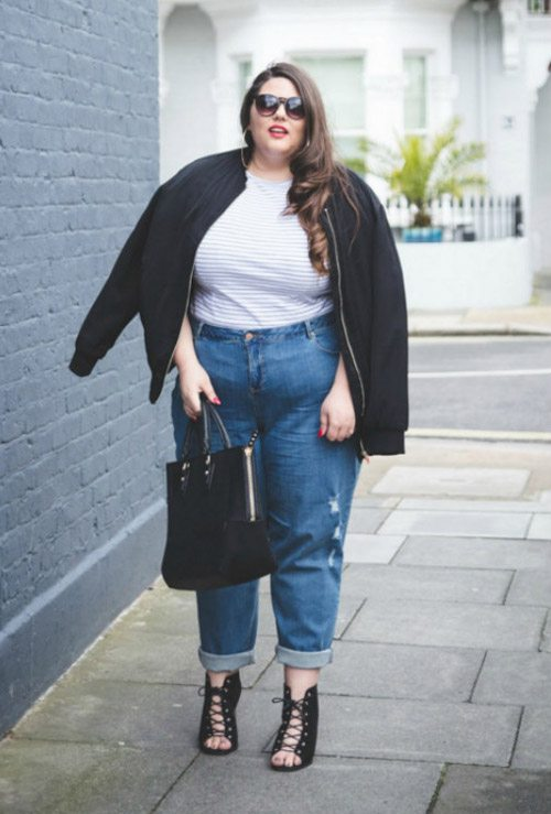 Полная девушка блогер в джинсах мом, бомбере и ботильонах