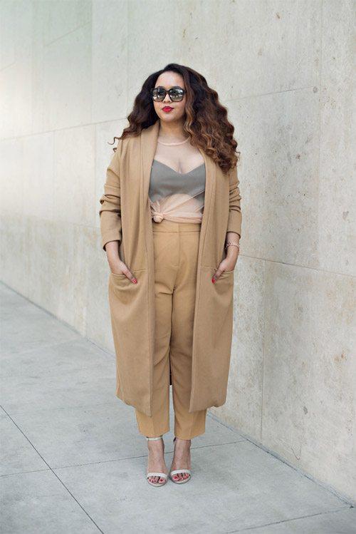 Полная девушка блогер в бежевых брюках, прозрачной блузке и длинном кардигане