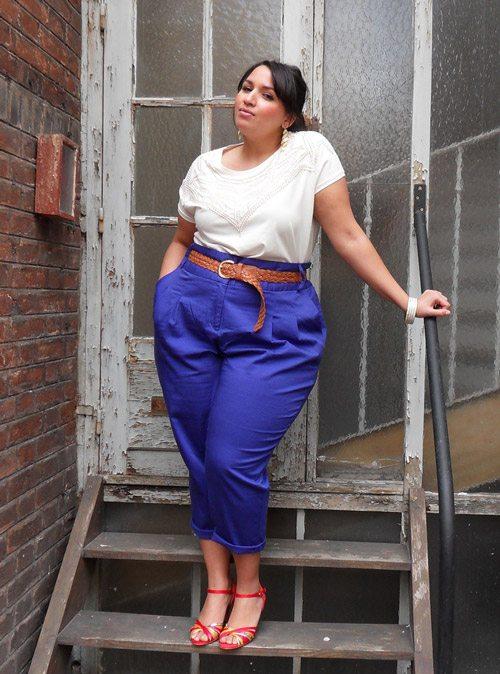 Полная девушка блогер в фиолетовых брюках, белой блузке и босоножках