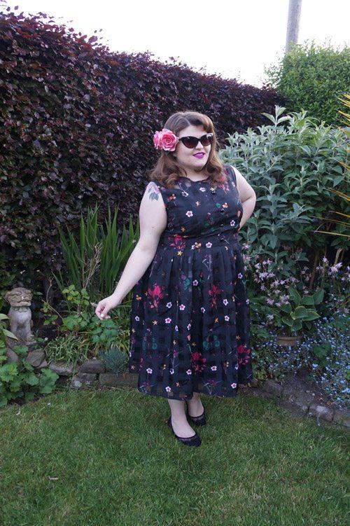 Полная девушка блогер в платье с цветочным принтом и солнцезащитных очках