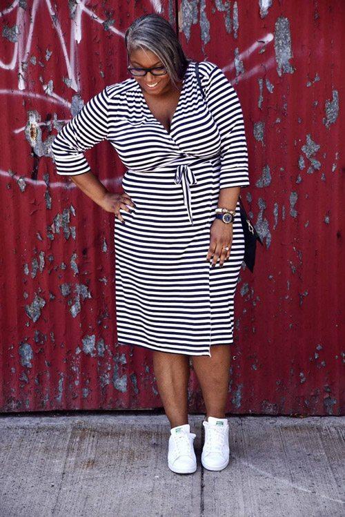 Полная девушка блогер в полосатом платье и кроссовках