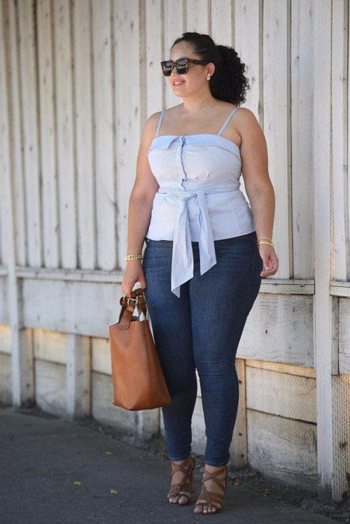 Полная девушка блогер в синих джинсах, топе и коричневых босоножках