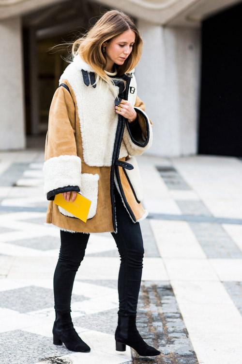 Девушка в кремово-белой дубленке, джинсах и ботильонах
