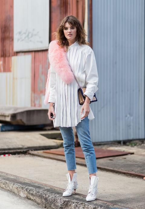 Девушка в белой удлиненной рубашке, джинсы, белые ботильоны и розовая накидка из меха