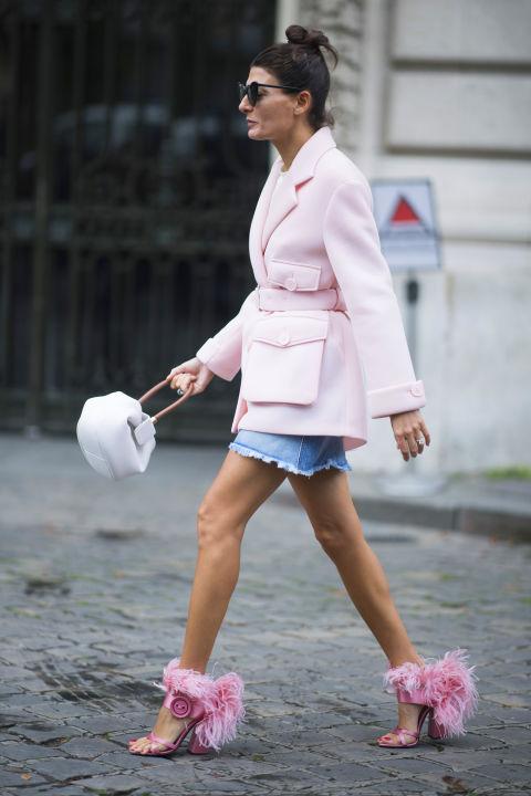 Девушка в джинсовой юбке, розовый кардиган и розовые босоножки с перьями