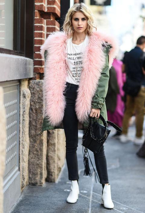 Девушка в парке с подкладом из розового меха, черные джинсы и белые ботильоны
