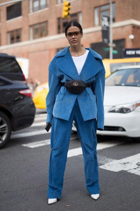Девушка в синем брючном костюме оверсайз и черной поясной сумке ремень