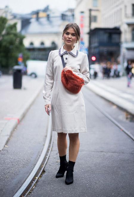 Девушка в светлом платье, черные ботильоны и меховая сумка
