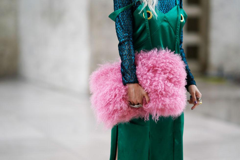 Девушка в зеленом сарафане и розовый макси клатч из искуcственного меха